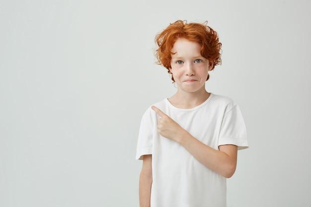 Porträt des schönen kleinen ingwerjungen mit sommersprossen mit schüchternem ausdruck, der mit finger beiseite zeigt. speicherplatz kopieren.