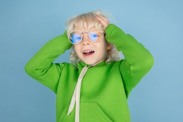 Porträt des schönen kleinen kaukasischen jungen lokalisiert auf blauem studiohintergrund. blondes lockiges männliches model. konzept des gesichtsausdrucks, der menschlichen emotionen, der kindheit, der anzeige, des verkaufs.