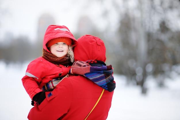Porträt des schönen kleinen kindes und seiner mutter im schneebedeckten park. junge familie mit kleinkindjungen genießen wintertag