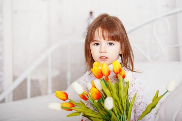 Porträt des schönen kleinen mädchens, das auf bett mit einem blumenstrauß der weißen und gelben tulpen sitzt