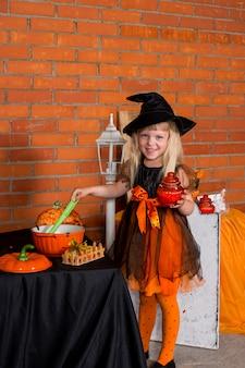 Porträt des schönen kleinen mädchens im orange schwarzen hexenhalloween-kostüm mit besen. happy halloween-konzept. süßes oder saures. lustige kinderparty, glückliche kindheit.