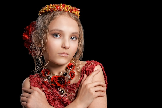 Porträt des schönen kleinen mädchens im roten kleid auf schwarzem hintergrund