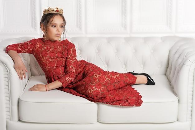 Porträt des schönen kleinen mädchens im roten kleid auf weißem hintergrund