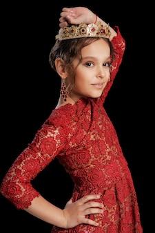 Porträt des schönen kleinen mädchens im roten kleid und in der krone auf schwarzem hintergrund