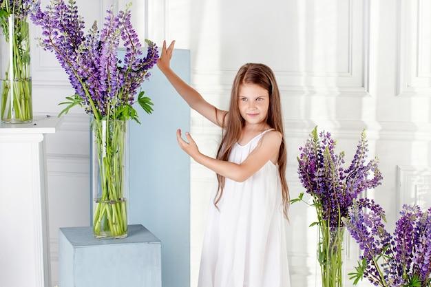 Porträt des schönen kleinen mädchens mit blumen. das mädchen lacht und spielt