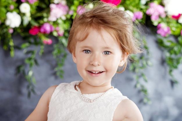 Porträt des schönen kleinen mädchens mit blumen. kamera betrachten