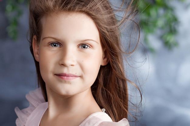 Porträt des schönen kleinen mädchens mit einem blumenstrauß. kamera betrachten. wind im haar. nahaufnahmebild