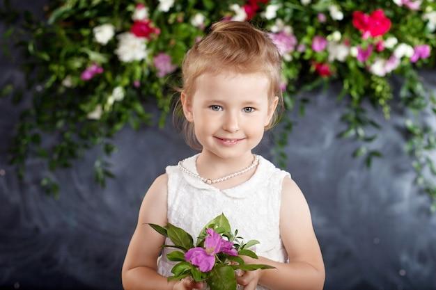 Porträt des schönen kleinen mädchens mit einem blumenstrauß. kamera betrachten.