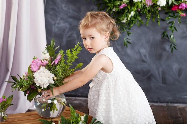 Porträt des schönen kleinen mädchens mit einem blumenstrauß