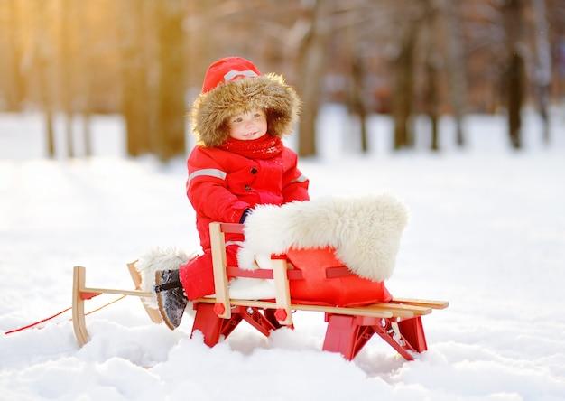 Porträt des schönen kleinkindjungen, der spaß im winterpark hat. spiel mit frischem schnee