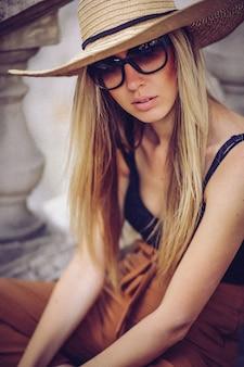 Porträt des schönen kühlen mädchens, das in hut und in sonnenbrille über schmutzwand gestikuliert