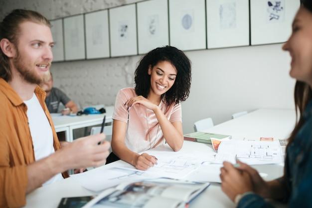 Porträt des schönen lächelnden afroamerikanischen mädchens mit dem dunklen lockigen haar, das mit freunden im büro sitzt