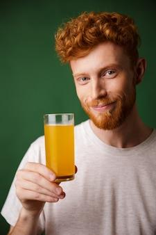 Porträt des schönen lächelnden bärtigen mannes, der glas orangensaft hält