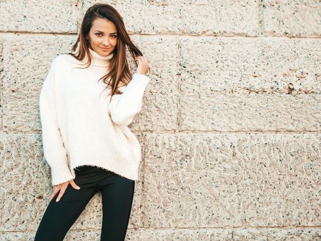 Porträt des schönen lächelnden baumusters. frau gekleidet in warmen hipster-weißen pullover. posiert in der nähe der wand auf der straße