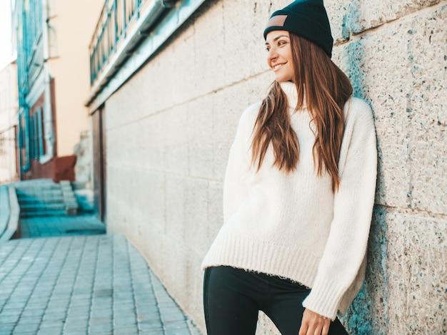 Porträt des schönen lächelnden baumusters. frau gekleidet in warmen hipster-weißen pullover und mütze. auf der straße posieren