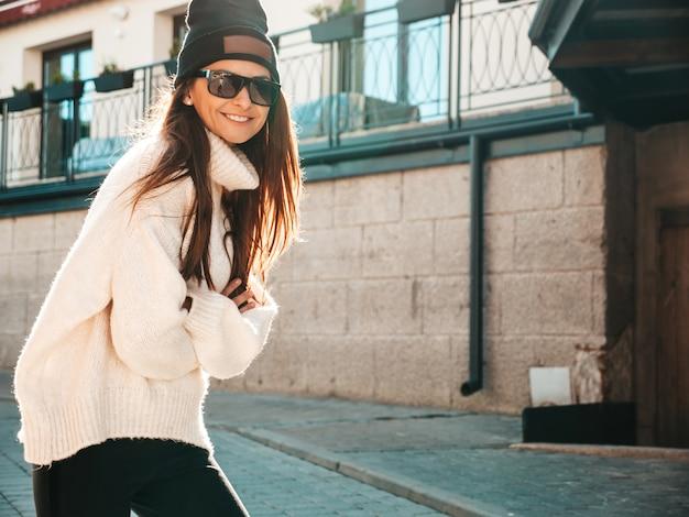 Porträt des schönen lächelnden baumusters. frau gekleidet in warmen hipster-weißen pullover und mütze. sie posiert auf der straße