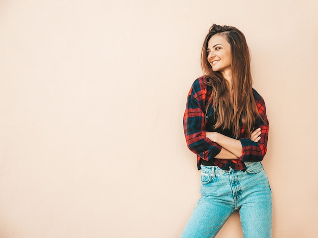 Porträt des schönen lächelnden baumusters. sexy frau gekleidet im sommer hipster kariertes hemd und jeans. trendiges mädchen posiert in der nähe der wand auf der straße
