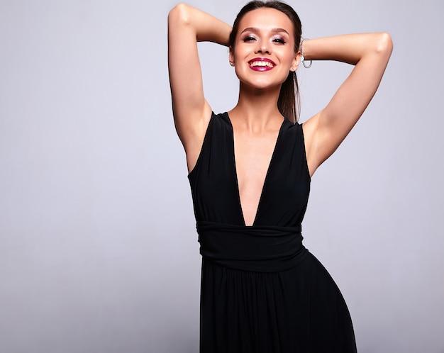 Porträt des schönen lächelnden brünetten frauenmodells im schwarzen kleid mit abendmake-up und und roten lippen lokalisiert auf grau