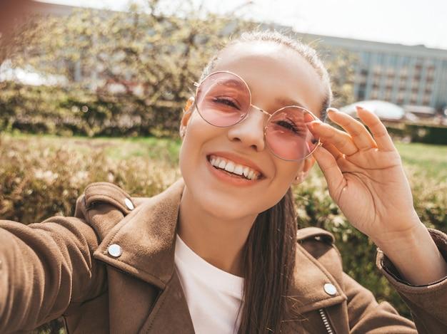 Porträt des schönen lächelnden brunettemädchens in der sommerhippie-jacke und in der jeanskleidung