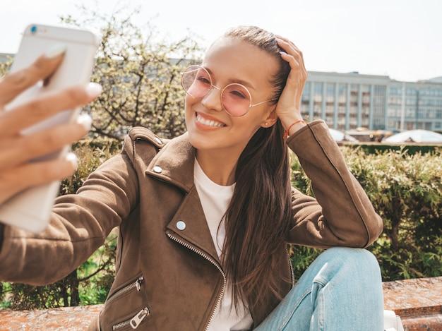 Porträt des schönen lächelnden brunettemädchens in der sommerhippie-jacke und -jeans modellieren das nehmen von selfie auf smartphone