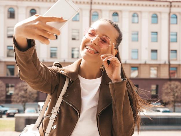 Porträt des schönen lächelnden brunettemädchens in der sommerhippie-jacke. vorbildliches nehmendes selfie auf smartphone. zeigen ihrer zunge