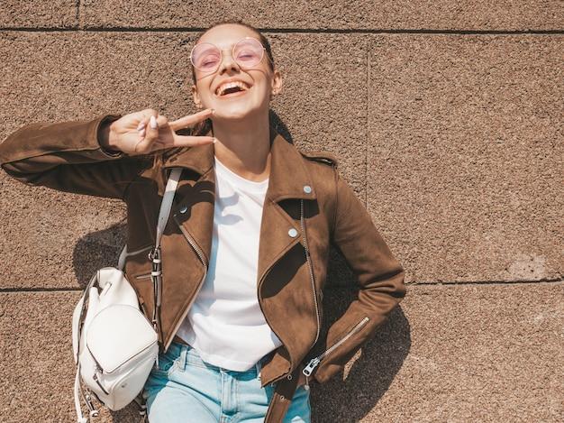Porträt des schönen lächelnden brunettemodells kleidete in der sommerhippie-jacke und in der jeanskleidung nahe wand an lustige und positive frau, die friedenszeichen zeigt
