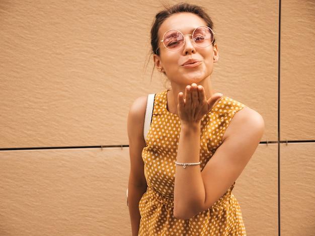Porträt des schönen lächelnden hippie-modells kleidete im sommergelbkleid an. modisches mädchen, das in der straße aufwirft. lustige und positive frau, die spaß hat. lässt luft küssen
