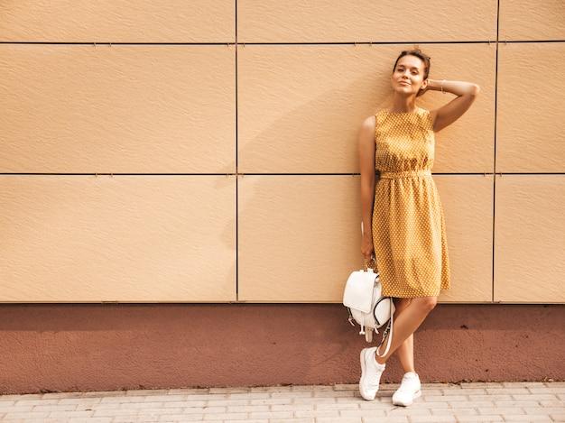 Porträt des schönen lächelnden hippie-modells kleidete im sommergelbkleid an. modisches mädchen, das in der straße aufwirft. lustige und positive frau, die spaß hat