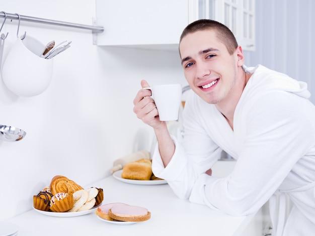Porträt des schönen lächelnden jungen mannes mit tasse in der küche