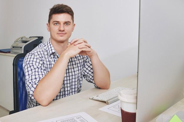 Porträt des schönen lächelnden jungen unternehmers, der am schreibtisch sitzt und vorne schaut
