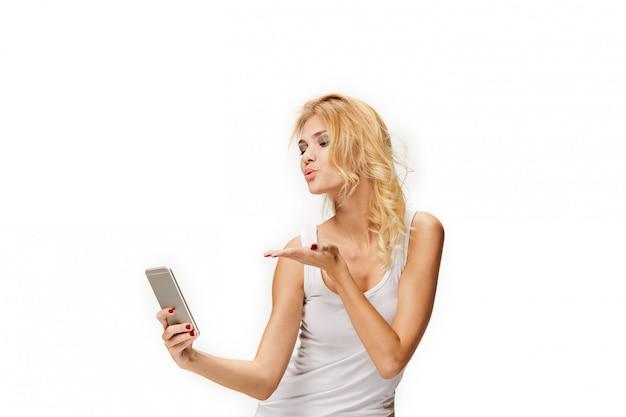 Porträt des schönen lächelnden mädchens mit dem modernen telefon