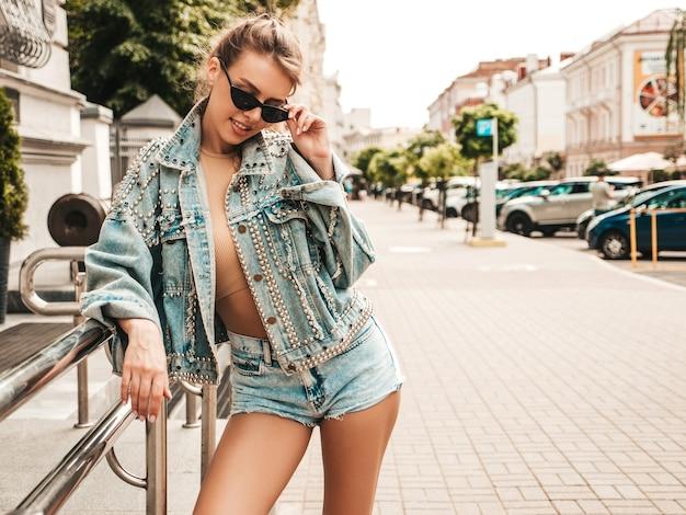Porträt des schönen lächelnden modells, das in der sommerhipster-jeansjacke gekleidet wird