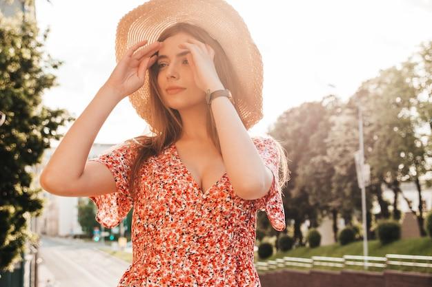 Porträt des schönen lächelnden modells gekleidet im sommer-hipster-kleid. sexy sorgloses mädchen, das im straßenhintergrund bei sonnenuntergang aufwirft. trendige lustige und positive frau im hut