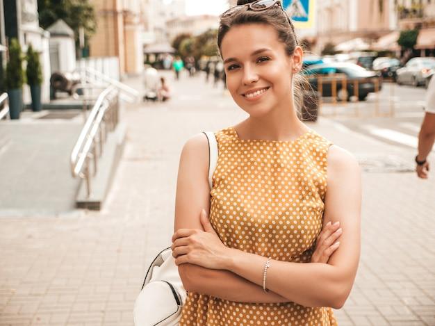 Porträt des schönen lächelnden modells kleidete im sommergelbkleid an. modisches mädchen, das in der straße aufwirft. lustige und positive frau, die spaß hat