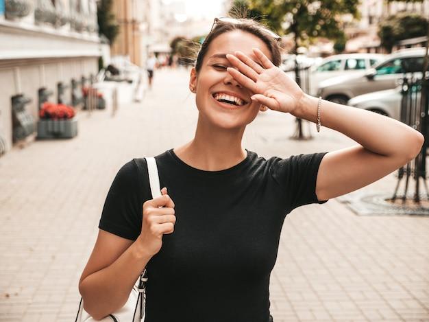 Porträt des schönen lächelnden modells kleidete in der sommerkleidung an. modisches mädchen, das in der straße aufwirft. lustige und positive frau, die spaß hat