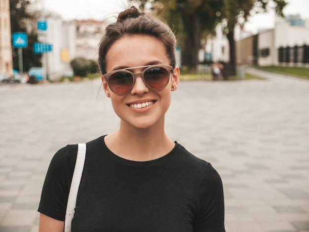 Porträt des schönen lächelnden modells kleidete in der sommerkleidung an. modisches mädchen, das in der straße in der sonnenbrille aufwirft. lustige und positive frau, die spaß hat