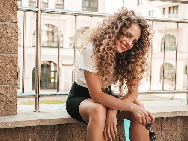 Porträt des schönen lächelnden modells mit afro-lockenfrisur gekleidet in sommer-hipster-kleidung. sexy sorgloses mädchen, das im straßenhintergrund sitzt. trendy lustige und positive frau, die spaß hat