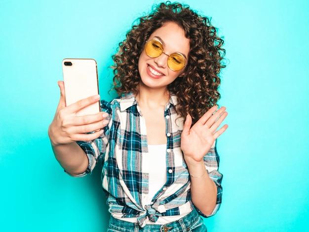 Porträt des schönen lächelnden modells mit afro-lockenfrisur gekleidet in sommer-hipster-kleidung. sexy sorgloses mädchen, das im studio auf grauem hintergrund aufwirft. trendige lustige frau macht selfie-foto