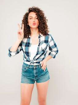 Porträt des schönen lächelnden modells mit afro-lockenfrisur gekleidet in sommer-hipster-kleidung. sexy sorgloses mädchen, das im studio auf grauem hintergrund aufwirft. trendige lustige und positive frau zeigt friedenszeichen