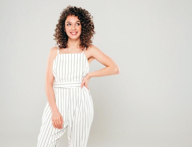 Porträt des schönen lächelnden modells mit afro-lockenfrisur gekleidet in sommer-hipster-kleidung. sexy sorgloses mädchen, das im studio auf grauem hintergrund aufwirft. trendige lustige und positive frau