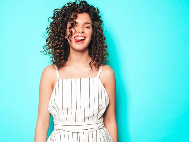 Porträt des schönen lächelnden modells mit afro-lockenfrisur gekleidet in sommer-hipster-kleidung. sexy sorgloses mädchen, das nahe blauer wand aufwirft. trendige lustige und positive frau. zeigt zunge