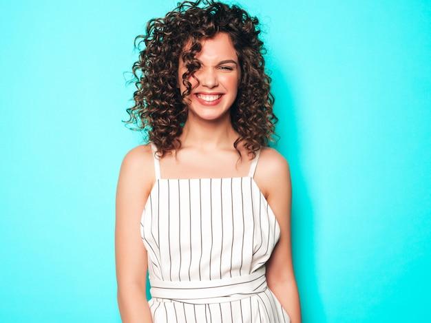 Porträt des schönen lächelnden modells mit afro-lockenfrisur gekleidet in sommer-hipster-kleidung. sexy sorgloses mädchen, das nahe blauer wand aufwirft. trendige lustige und positive frau