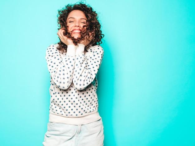 Porträt des schönen lächelnden modells mit afro-lockenfrisur gekleidet in sommer-hipster-kleidung. trendige lustige und positive frau im weißen kapuzenpulli