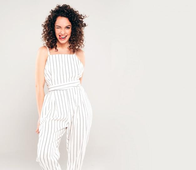 Porträt des schönen lächelnden modells mit afro-lockenfrisur gekleidet in sommer-hipster-kleidung. trendige lustige und positive frau zeigt zunge