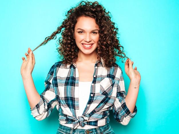 Porträt des schönen lächelnden modells mit afro-lockenfrisur gekleidet in sommer-hipster-kleidung. trendige lustige und positive frau