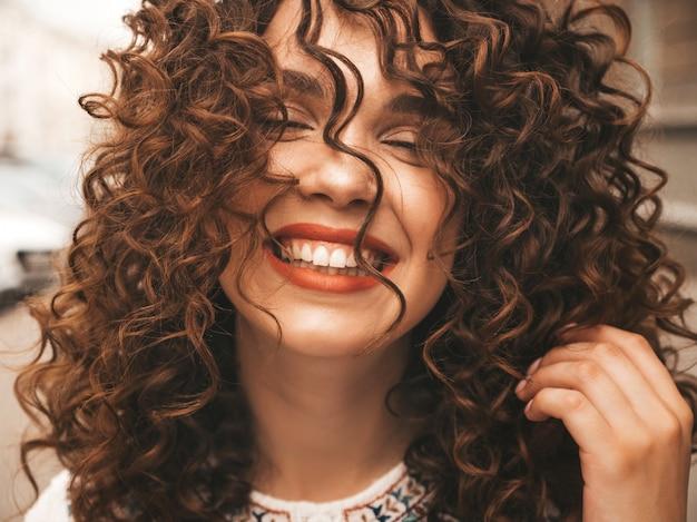 Porträt des schönen lächelnden modells mit afrolockenfrisur.