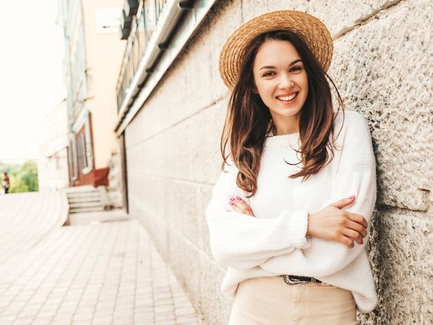 Porträt des schönen lächelnden netten modells. frau gekleidet in warmen hipster weißen pullover und hut. posiert in der nähe der wand auf der straße. lustige und positive frau, die sich umarmt