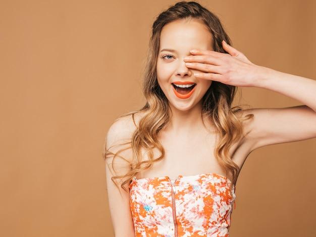 Porträt des schönen lächelnden netten modells mit den rosa lippen. mädchen im bunten sommerkleid. model posiert. bedeckte ihr auge mit der hand