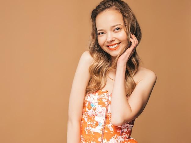 Porträt des schönen lächelnden netten modells mit den rosa lippen. mädchen im bunten sommerkleid. model posiert