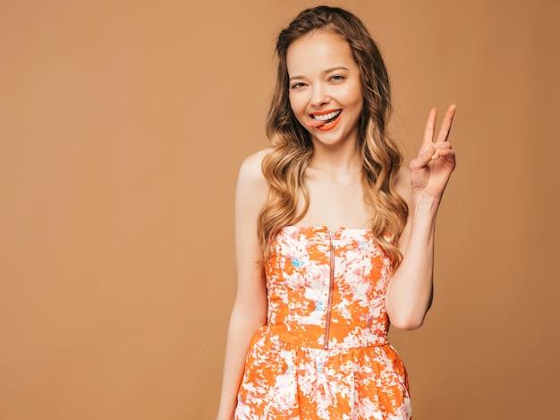 Porträt des schönen lächelnden netten modells mit den rosa lippen. mädchen im bunten sommerkleid. vorbildliche aufstellung. zeigen des friedenszeichens